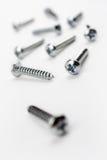 Mittlere Längen-Eisen-Schrauben in einem weißen Kasten - gekrümmter Winkel Lizenzfreie Stockfotografie