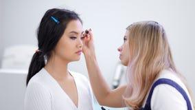 Mittlere Nahaufnahme Berufs-visagiste, das Augenbrauenmake-up für den weiblichen Kunden verwendet Bürste macht stock video footage