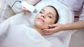 Mittlere Nahaufnahmehände von Cosmetologist Schönheit Gesichtsverfahren mit moderner Schälerausrüstung machend stock footage