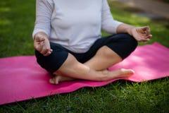 Mittlerer Abschnitt der älteren Frau meditierend auf Übungsmatte Lizenzfreies Stockfoto