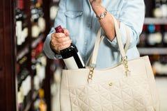 Mittlerer Abschnitt der älteren Frau Weinflasche in die Tasche einsetzend Stockfoto