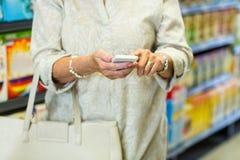 Mittlerer Abschnitt der Frau, die Smartphone verwendet Lizenzfreie Stockbilder