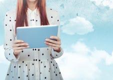 Mittlerer Abschnitt der Frau mit Tupfenspitze und Tablette gegen Himmel mit Aufflackern Stockfotografie