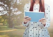 Mittlerer Abschnitt der Frau mit Tupfenspitze und Tablette gegen Park mit Aufflackern Lizenzfreie Stockfotografie