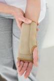 Mittlerer Abschnitt der Nahaufnahme einer Frau mit der Hand in der Handgelenkklammer Stockfotografie