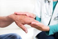 Mittlerer Abschnitt der Nahaufnahme eines Doktors, der Patientenhände hält Stockbild