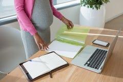 Mittlerer Abschnitt der schwangeren Frau arbeitend am Schreibtisch Stockfotos
