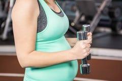 Mittlerer Abschnitt der schwangeren Frau Dummköpfe halten Stockfotografie