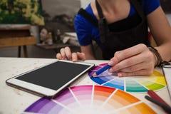 Mittlerer Abschnitt der zusammenpassenden Farbe der Frau mit Farbmuster Lizenzfreies Stockfoto