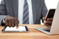Mittlerer Abschnitt des Geschäftsmannes unter Verwendung der digitalen Tablette und anderer Multimediageräte Lizenzfreie Stockfotos