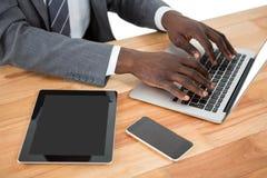 Mittlerer Abschnitt des Geschäftsmannes unter Verwendung des Laptops und anderer Multimediageräte Stockfotos