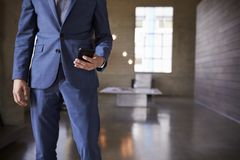Mittlerer Abschnitt des Mannes in der blauen Klage unter Verwendung des Smartphone stockbilder