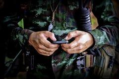 Mittlerer Abschnitt des Militärsoldaten, der Handy im Ausbildungslager verwendet stockbild