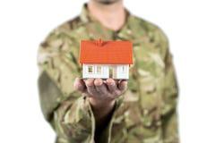 Mittlerer Abschnitt des Soldaten ein Musterhaus halten lizenzfreies stockfoto