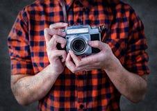 Mittlerer Abschnitt des tausendjährigen Mannes mit Kamera gegen grauen Hintergrund mit Schmutzüberlagerung Lizenzfreie Stockfotografie