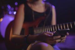 Mittlerer Abschnitt des weiblichen Gitarristen, der Mobile verwendet Lizenzfreie Stockbilder