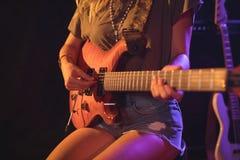 Mittlerer Abschnitt des weiblichen Gitarristen im Konzert Stockfotografie