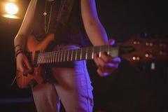 Mittlerer Abschnitt des weiblichen Gitarristen im Musikkonzert Lizenzfreies Stockfoto