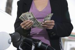 Mittlerer Abschnitt einer Frau, die ihr Auto bei der Zählung des Geldes wieder tankt Lizenzfreies Stockbild