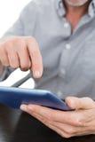 Mittlerer Abschnitt eines Geschäftsmannes unter Verwendung der digitalen Tablette bei Tisch Stockbilder