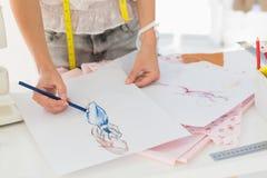 Mittlerer Abschnitt eines Modedesigners, der an ihren Designen arbeitet Stockfotos