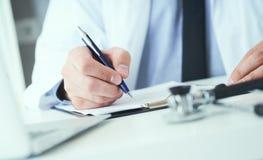 Mittlerer Abschnitt männlichen Doktors schreibt dem Patienten Verordnung am Worktable Allheilmittel und Lebenabwehr, vorschreiben stockbild