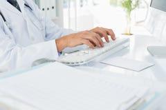 Mittlerer Abschnitt von Doktor, der Computertastatur im Ärztlichen Dienst verwendet Stockfotografie