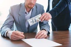 Mittlerer Beamter, der seinem Kollegen ein Bestechungsgeld gibt stockfotos