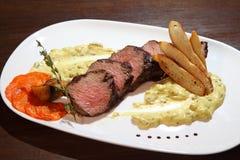 Mittlerer Braten des appetitanregenden Steaks, Schnitt in Stücke in der sahnigen Pilzsoße Steak diente auf weißer Platte auf eine Lizenzfreies Stockbild