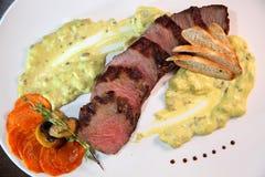 Mittlerer Braten des appetitanregenden Steaks, Schnitt in Stücke in der sahnigen Pilzsoße Steak diente auf weißer Platte auf eine Lizenzfreie Stockfotos