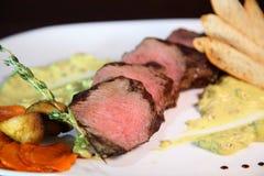 Mittlerer Braten des appetitanregenden Steaks, Schnitt in Stücke in der sahnigen Pilzsoße Steak diente auf weißer Platte auf eine Stockfotos