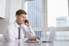 Mittlerer erwachsener Geschäftsmann beim Anruf bei Laptop zu Hause verwenden lizenzfreie stockfotos
