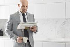 Mittlerer erwachsener Geschäftsmann, der Kaffee beim Ablesen der Zeitung in der Küche trinkt stockfotos