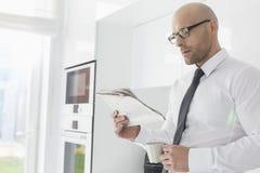 Mittlerer erwachsener Geschäftsmann, der Kaffee beim Zeitung zu Hause lesen trinkt stockfoto