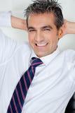 Mittlerer erwachsener Geschäftsmann Relaxing With Hands hinten Stockbild