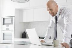 Mittlerer erwachsener Geschäftsmann unter Verwendung des Laptops an der Küchenarbeitsplatte stockfoto