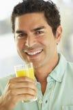Mittlerer erwachsener Mann, der ein Glas Orangensaft anhält stockbild