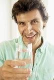 Mittlerer erwachsener Mann, der ein Glas Wasser trinkt Stockfotos
