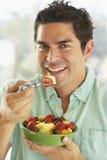 Mittlerer erwachsener Mann, der eine Schüssel frischen Fruchtsalat anhält lizenzfreie stockfotos