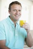 Mittlerer erwachsener Mann, der Orangensaft trinkt Stockfotos