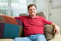 Mittlerer erwachsener Mann, der sich zu Hause entspannt stockbild