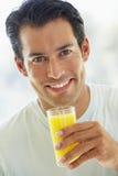 Mittlerer erwachsener Mann-lächelnder trinkender Orangensaft Lizenzfreie Stockfotos