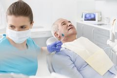 Mittlerer erwachsener Zahnarzt mit der Ausrüstung, die älteren Patienten an der Klinik behandelt lizenzfreie stockfotografie