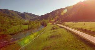 Mittlerer Flug über frischem Gebirgsfluss und Wiese am sonnigen Sommermorgen Ländlicher Schotterweg unten Lizenzfreie Stockfotos