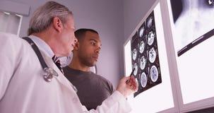 Mittlerer gealterter Arzt, der x-Strahl des afrikanischen Patienten wiederholt lizenzfreie stockbilder