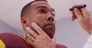 Mittlerer gealterter Doktor, der die Augen des Fußballspielers mit Taschenlampe überprüft stockfoto