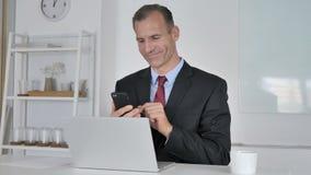 Mittlerer gealterter Geschäftsmann Using Smartphone für on-line-Finanzhandel stock footage
