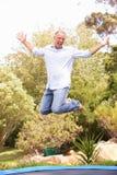 Mittlerer gealterter Mann, der auf Trampoline im Garten springt Lizenzfreies Stockfoto