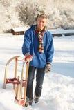 Mittlerer gealterter Mann, der in der Snowy-Landschaft steht Lizenzfreie Stockfotos