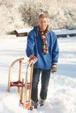Mittlerer gealterter Mann, der in der Snowy-Landschaft steht Stockfoto